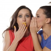 Young woman whispers to her friend_iStock_000059672604_Large