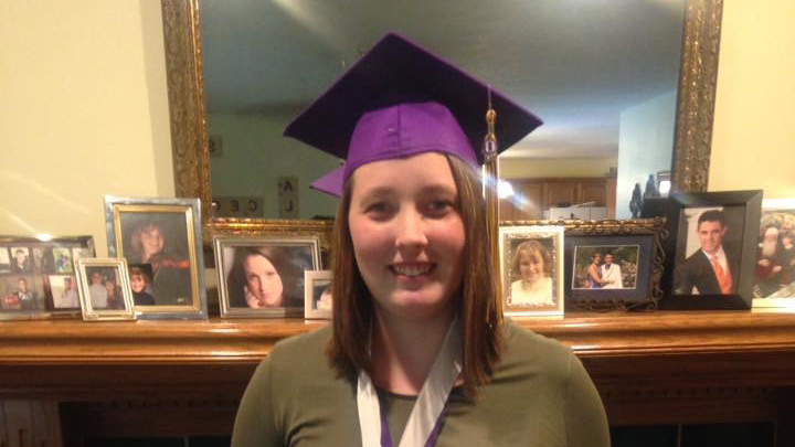 Smiling girl in front of a fireplace mantle wearing a graduation cap