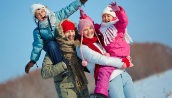 Ecstatic family looking at camera in winter