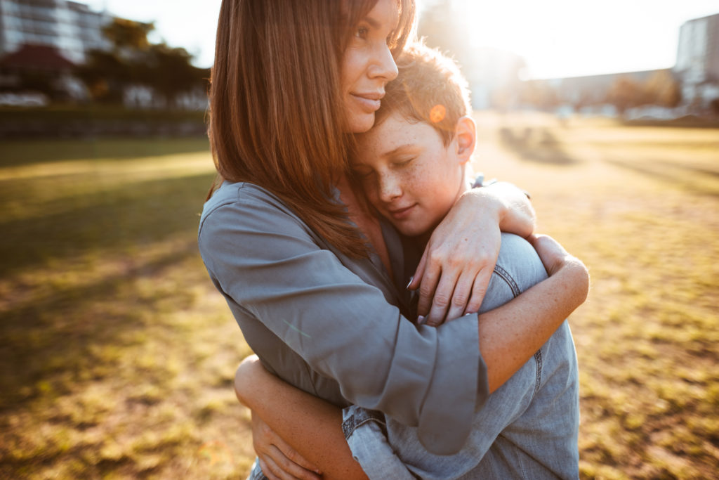 teenager embraced with mom consoling her son