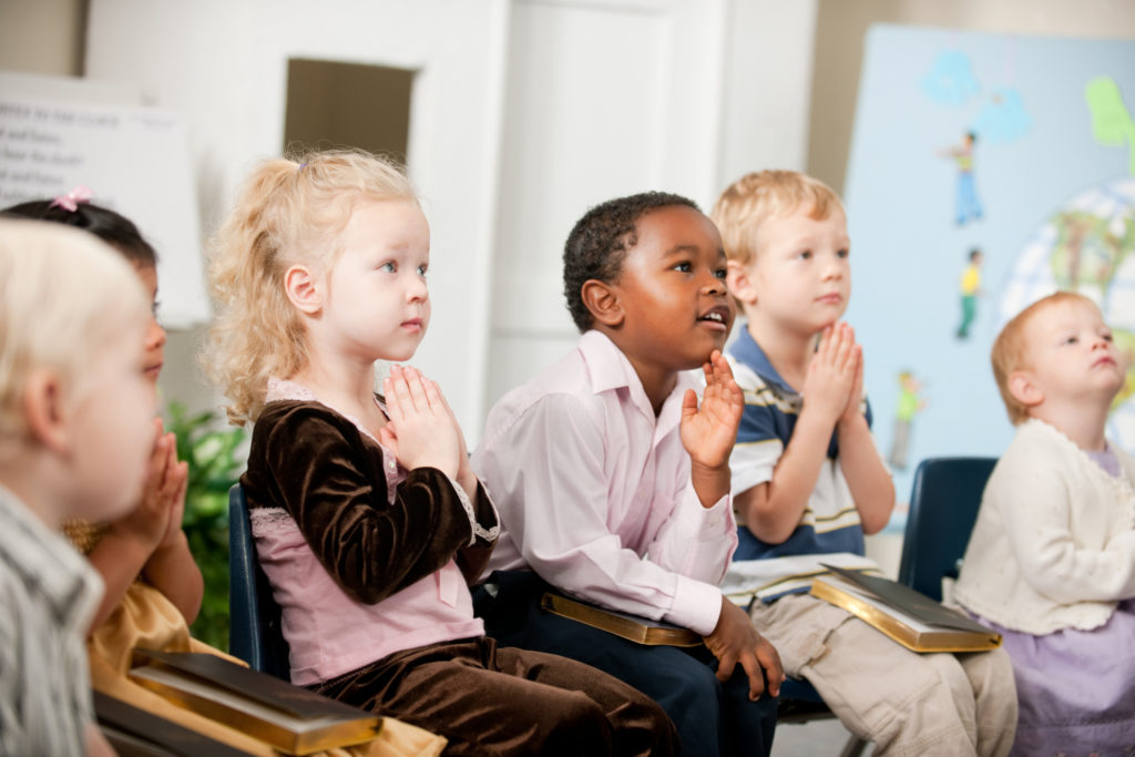 A group of multi-ethnic children at Sunday School in a real church classroom.