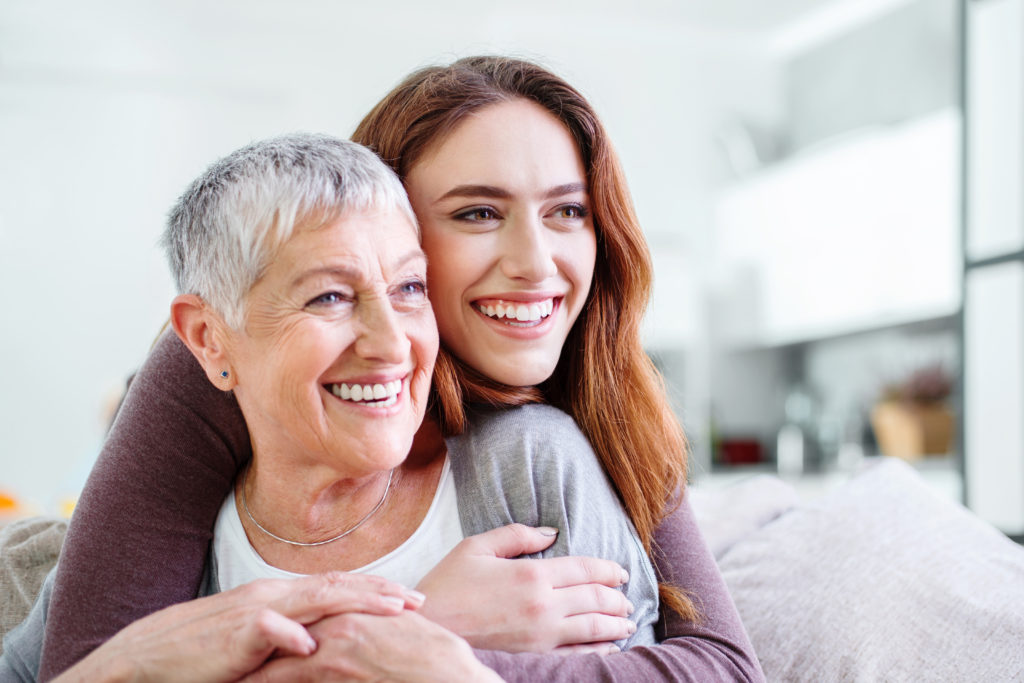 Young woman holding affectionately her mother, both are smiling happily, with copy space