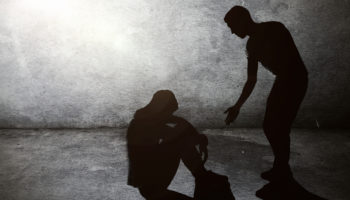 A silhouette of a man reaching out to help assist another person who is sitting on the ground with his head looking toward the ground in sadness or depression. The background is a dark concrete urban setting, lit by a single light from above. Meant to depict aid, assistance, charity, relief work, and care for the needy, homeless, and troubled. Horizontal with copy space.