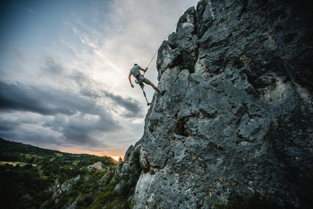 Man with prosthetic leg free mountain climbing