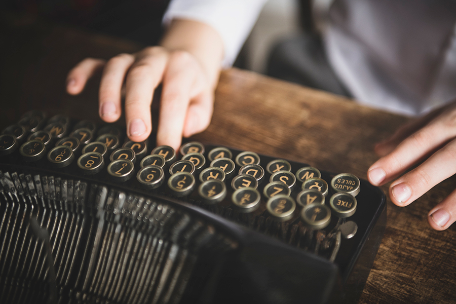 Hands typing on an old fashioned typewriter