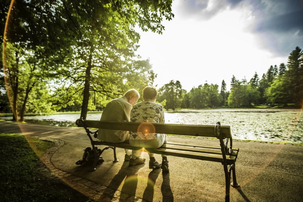 Senior couple sitting on a bench next to a lake in a park