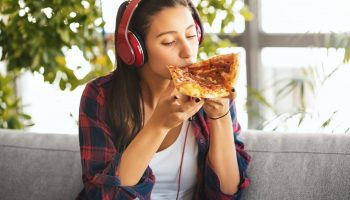 Teenage girl sitting on the sofa. Shes's wearing headphones, listening to the musing and eating pizza.